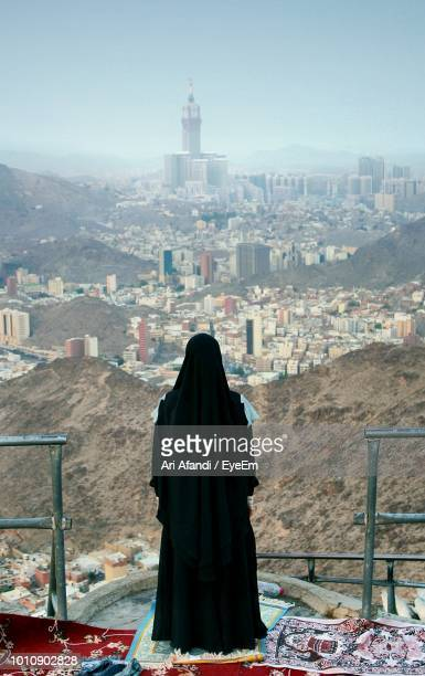 rear view of woman wearing black dress while standing against cityscape - gulf countries stock pictures, royalty-free photos & images