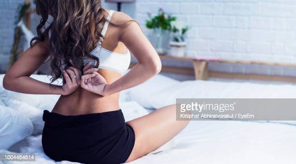 rear view of woman wearing bra on bed at home - lingerie stock pictures, royalty-free photos & images