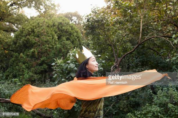 Rear view of woman wearing crown and orange scarf against trees at park
