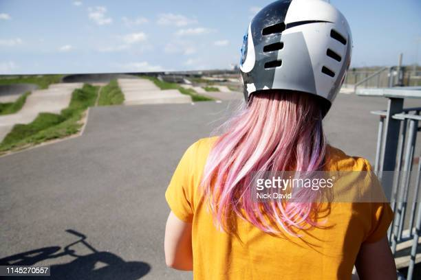 rear view of woman wearing cycling helmet facing track - bmx track london stock pictures, royalty-free photos & images