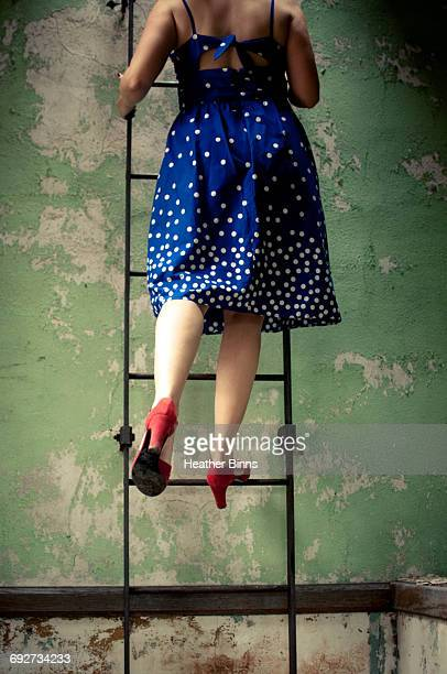 Rear view of woman wearing dress and high heels climbing ladder