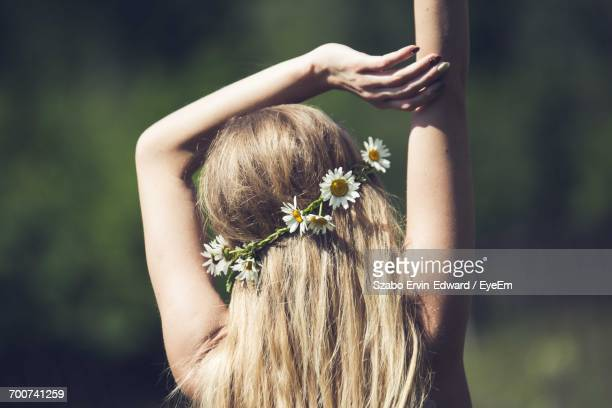 Rear View Of Woman Wearing Flowers On Hair During Sunny Day