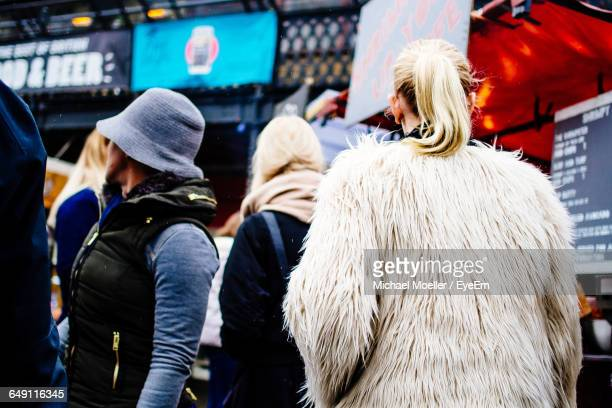 rear view of woman wearing fur coat - fur coat stock pictures, royalty-free photos & images