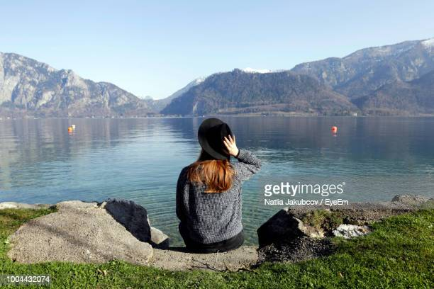 rear view of woman wearing hat sitting at lakeshore against mountains - riva del lago foto e immagini stock