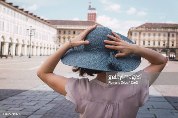 rear view of woman wearing hat standing against buildings in city - turin stock pictures, royalty-free photos & images