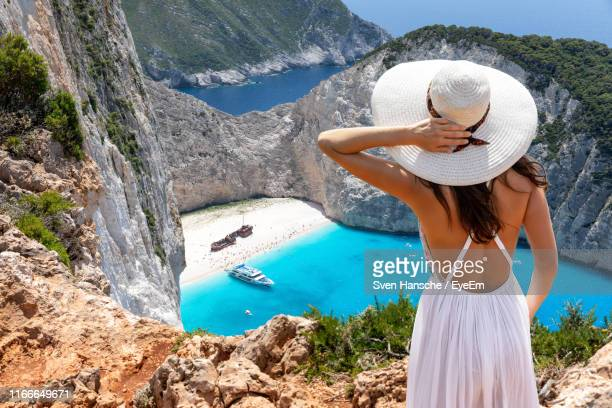 rear view of woman wearing hat standing on cliff - greek islands stock pictures, royalty-free photos & images