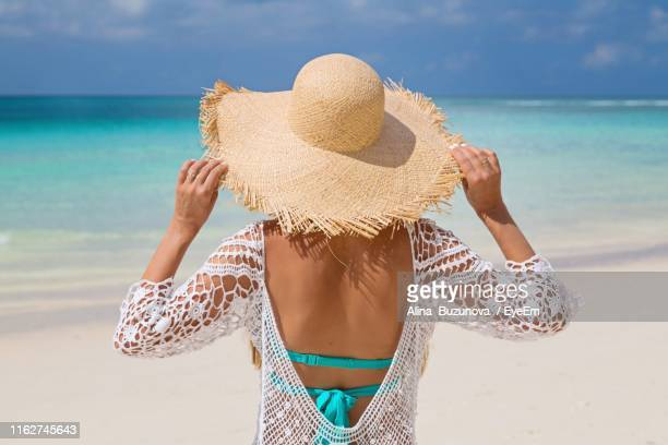 rear view of woman wearing hat while standing at beach - backless stock pictures, royalty-free photos & images