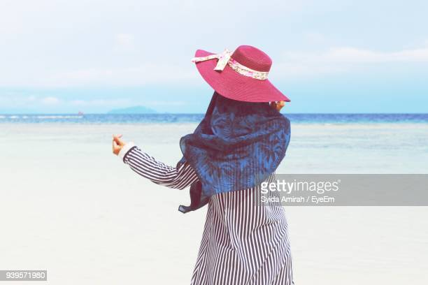Rear View Of Woman Wearing Hat While Standing At Beach