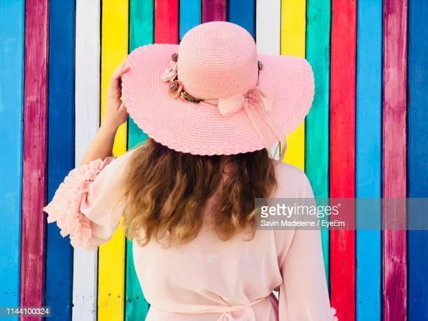 rear view of woman wearing hat while standing by colorful wall - lady madeleine stock-fotos und bilder