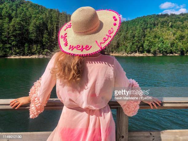 rear view of woman wearing hat while standing by lake against mountains and sky - lady madeleine stock-fotos und bilder