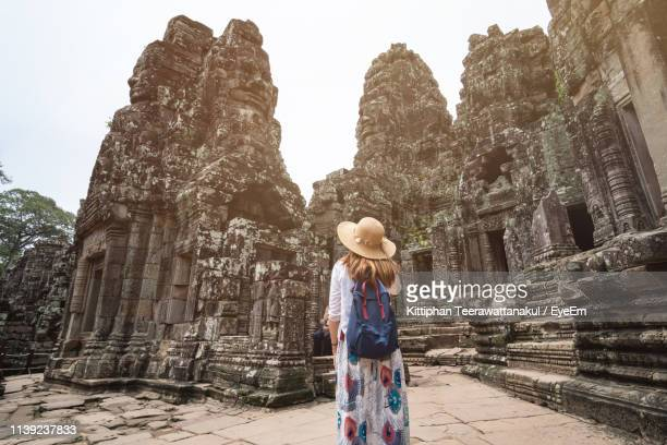 rear view of woman wearing hat while standing by old temple - old ruin stock pictures, royalty-free photos & images