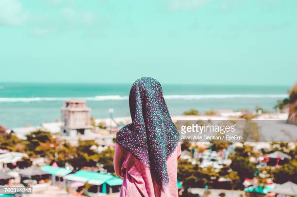 Rear View Of Woman Wearing Hijab Looking At View While Standing At Beach