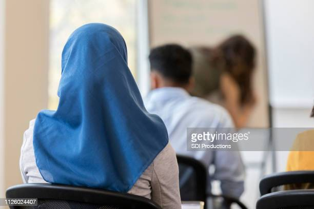 rear view of woman wearing hijab sitting in classroom - wedding veil stock photos and pictures