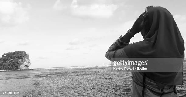 Rear View Of Woman Wearing Hijab Standing At Beach Against Sky