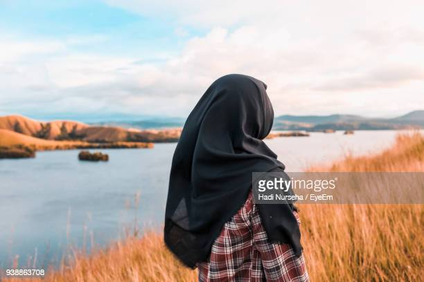 Rear View Of Woman Wearing Hijab Standing By Lake Against Sky