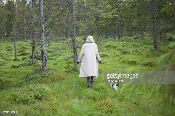 Rear view of woman wearing long coat while walking with cat on grassy field