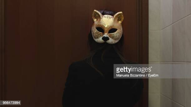 rear view of woman wearing mask against wall - manuela maske stock-fotos und bilder