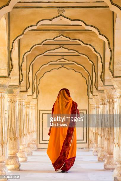 rear view of woman wearing orange sari walking along a colonnade. - rajasthan stock pictures, royalty-free photos & images