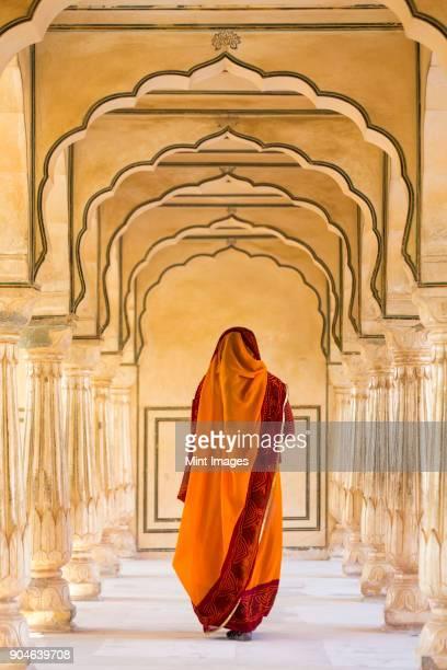 rear view of woman wearing orange sari walking along a colonnade. - rajastão imagens e fotografias de stock