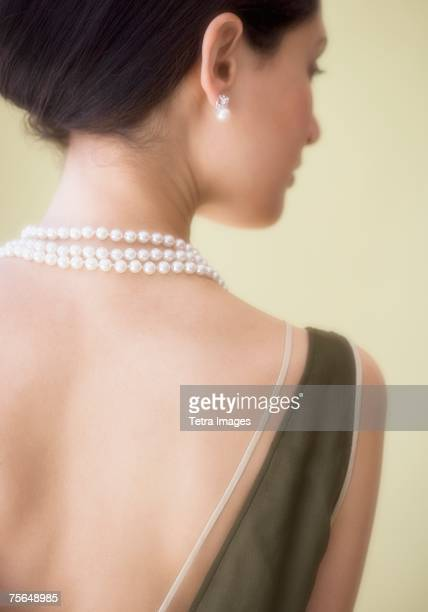 rear view of woman wearing pearl necklace - pearl necklace stock pictures, royalty-free photos & images
