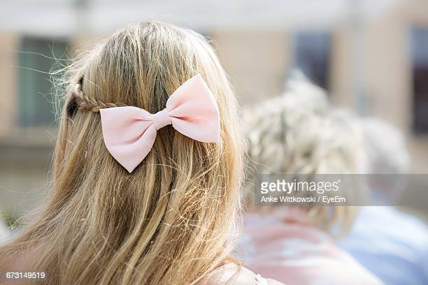 Rear View Of Woman Wearing Pink Tied Bow In Hair