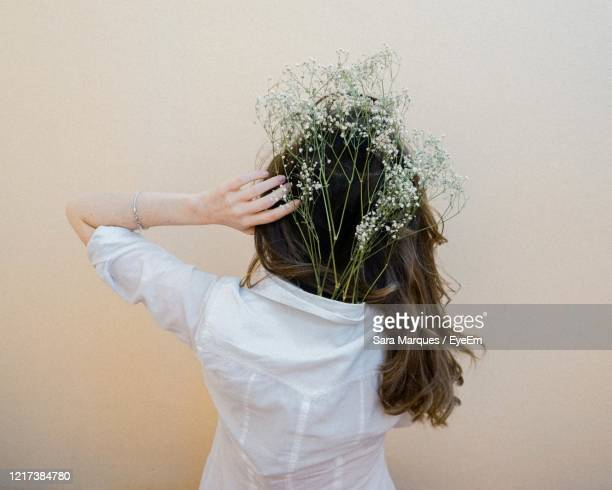 rear view of woman wearing plants in shirt while standing against wall - long stem flowers stock pictures, royalty-free photos & images