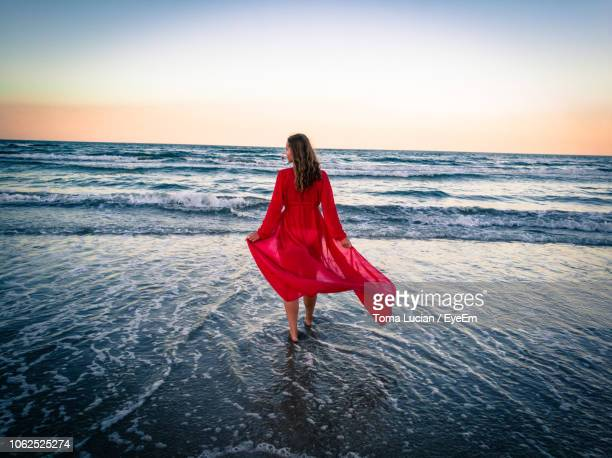 rear view of woman wearing red dress walking on shore at beach against sky during sunset - vestito da donna foto e immagini stock