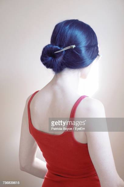 rear view of woman wearing red tank top while standing by wall - débardeur photos et images de collection