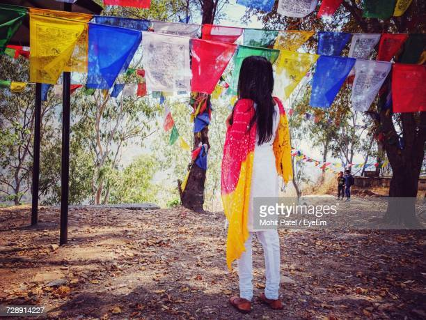 rear view of woman wearing salwar kameez looking at prayer flags hanging from trees - salwar kameez stock pictures, royalty-free photos & images