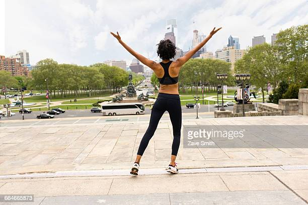 rear view of woman wearing sports clothing, arms raised looking at city - filadélfia pensilvânia - fotografias e filmes do acervo