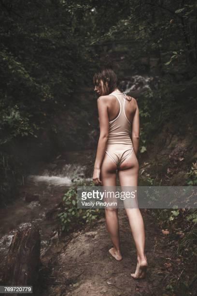 Rear view of woman wearing swimwear walking on pathway by stream in forest