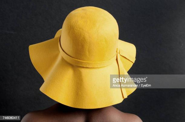 rear view of woman wearing yellow floppy hat against black background - drooping stock photos and pictures