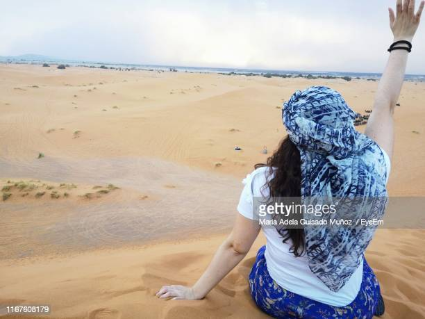 rear view of woman with arm raised sitting on sandy beach against sky - femme marocaine photos et images de collection