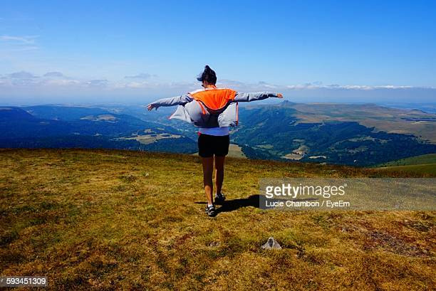 rear view of woman with arms outstretched on mountain against blue sky - auvergne stock pictures, royalty-free photos & images