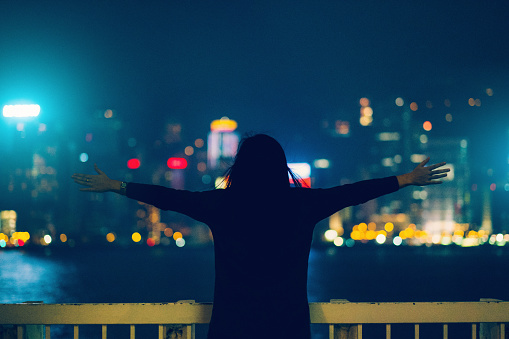 Rear view of woman with arms outstretched over illuminated city skyline of Hong Kong at night - gettyimageskorea