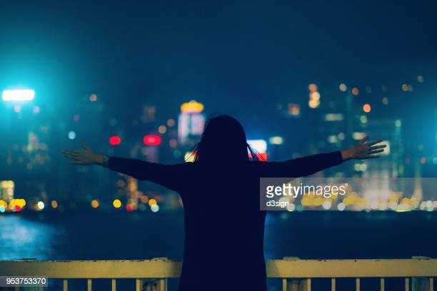 Rear view of woman with arms outstretched over illuminated city skyline of Hong Kong at night
