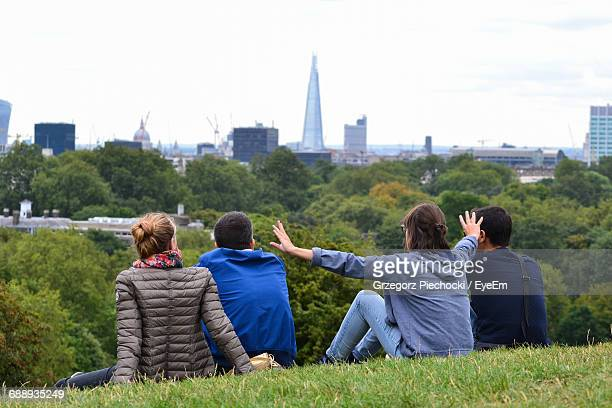 Rear View Of Woman With Arms Outstretched Standing Amidst Friends In Park