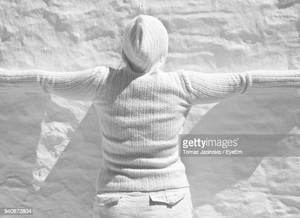 Rear View Of Woman With Arms Outstretched Standing By White Wall