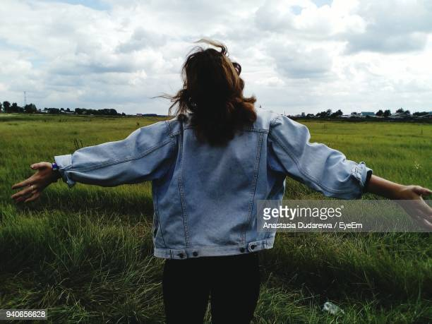 rear view of woman with arms outstretched standing on grassy field - denim jacket stock pictures, royalty-free photos & images