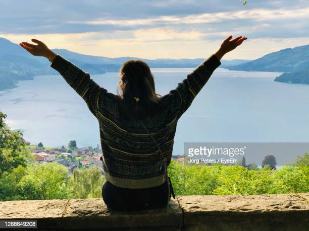 "rear view of woman with arms outstretched standing on landscape at lake thun - ""jörg peters"" stock-fotos und bilder"