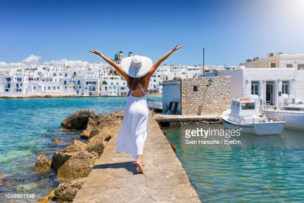 rear view of woman with arms outstretched walking on pier in sea - greece stock pictures, royalty-free photos & images