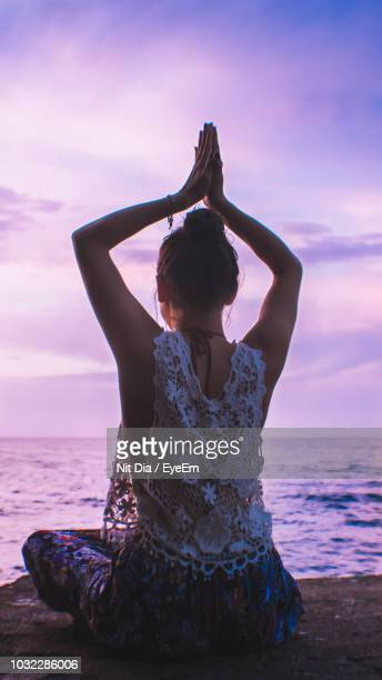 Rear View Of Woman With Arms Raised Meditating At Beach Against Sky During Sunset