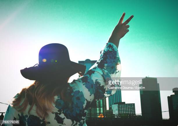 Rear View Of Woman With Arms Raised Showing Peace Sign While Standing In City