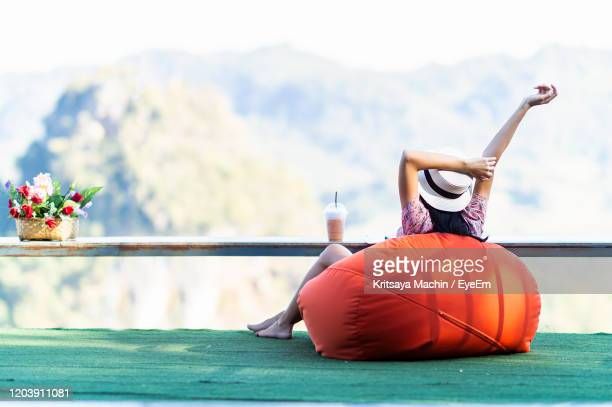 rear view of woman with arms raised sitting on bean bag - sacco photos et images de collection
