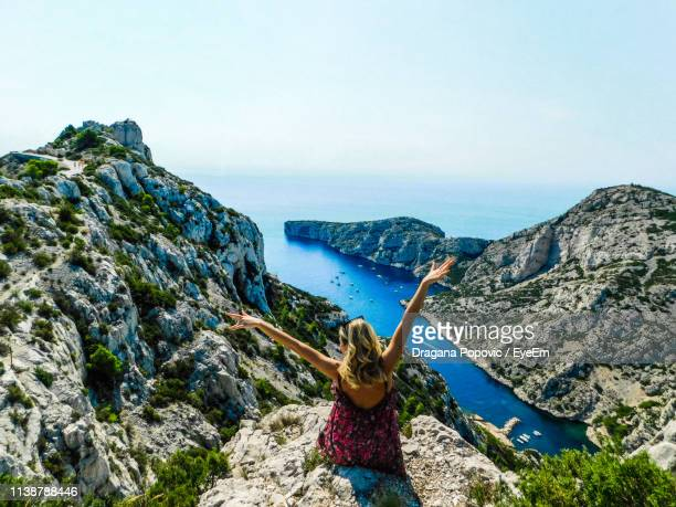 rear view of woman with arms raised sitting on cliff by sea against sky - marseille stock pictures, royalty-free photos & images