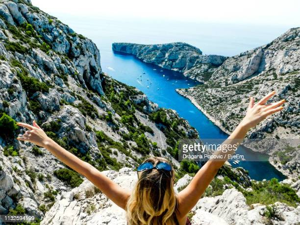 rear view of woman with arms raised sitting on cliff by sea - marseille stock pictures, royalty-free photos & images