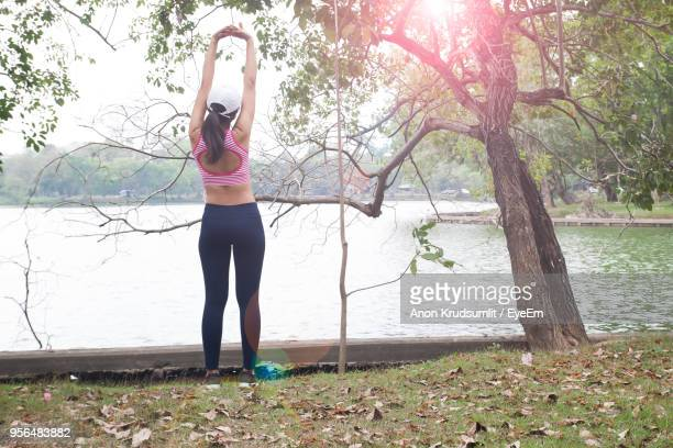 Rear View Of Woman With Arms Raised Standing Against Lake