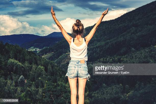 rear view of woman with arms raised standing against mountains - arme hoch stock-fotos und bilder