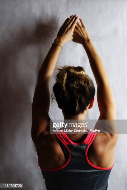 rear view of woman with arms raised standing against wall - morten müller schnelle stock-fotos und bilder