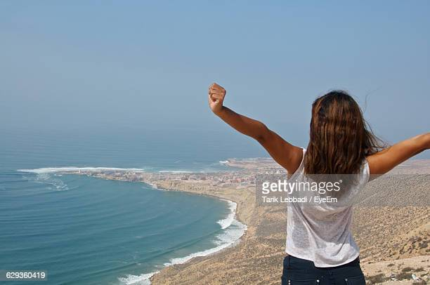 rear view of woman with arms raised standing by beach against sky - agadir stock pictures, royalty-free photos & images